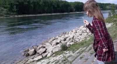 Sonntagsausflug an den Rhein. Mädchen steht am Wasser