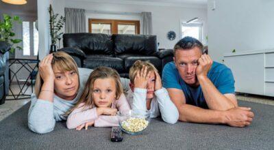 Eine Familie sitzt im Lockdown auf dem Boden im Wohnzimmer und langweilt sich.