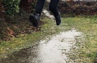 Ein Mädchen springt in eine Pfütze