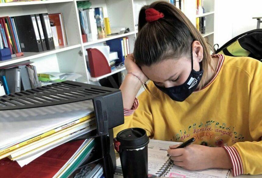 Mädchen mit Maske sitzt am Schreibntisch