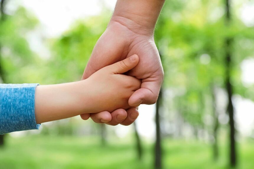 Little child holding hands with his father outdoors, closeup. Family time